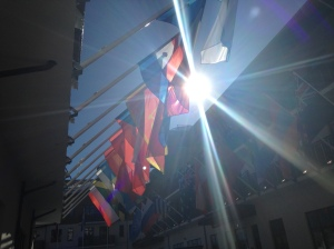 The sun shines through the flags waving at the Athletes' Village.